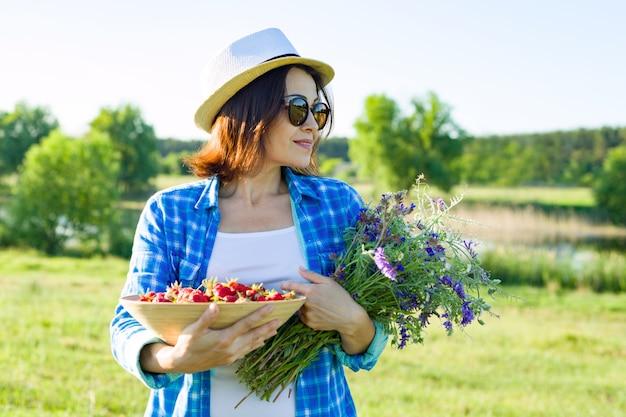 Retrato ao ar livre do verão de mulher com morangos