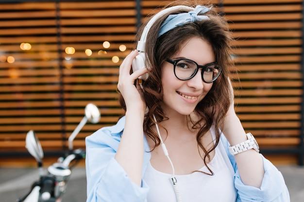 Retrato ao ar livre em close-up de uma linda garota sorridente de óculos tocando fones de ouvido brancos