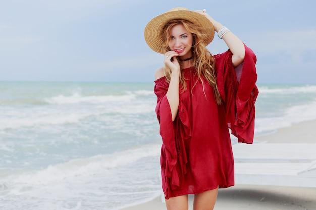 Retrato ao ar livre estilo de vida de mulher de gengibre branco e elegante vestido elegante posando na praia perto do oceano. céu azul. tempo ventoso.