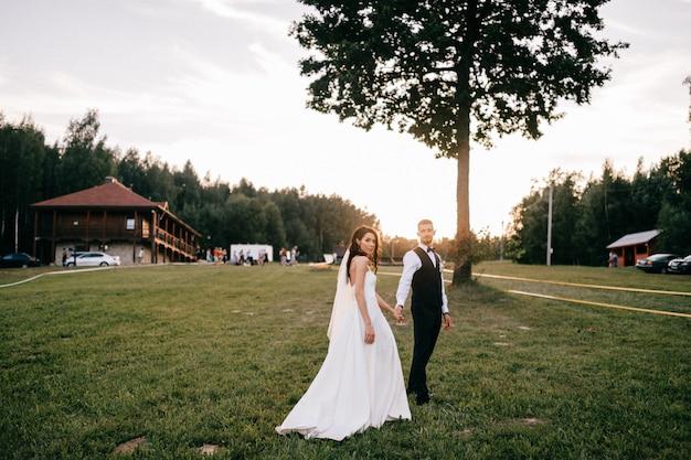 Retrato ao ar livre lindo casal de noivos. noiva bonita nova que abraça o noivo no por do sol contra o encapement