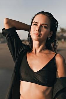 Retrato ao ar livre na moda de uma mulher bonita e atraente com cabelo escuro e olhos azuis, olhando para o oceano à luz do sol