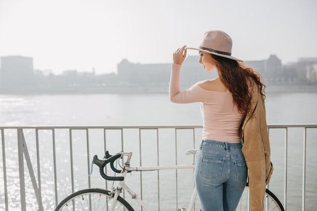 Retrato ao ar livre na parte de trás de uma mulher romântica de cabelos compridos apreciando a vista da cidade pela manhã