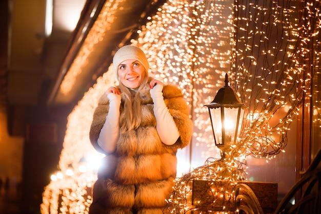 Retrato ao ar livre perto de jovem sorridente feliz posando na rua. queda de neve, guirlanda festiva.