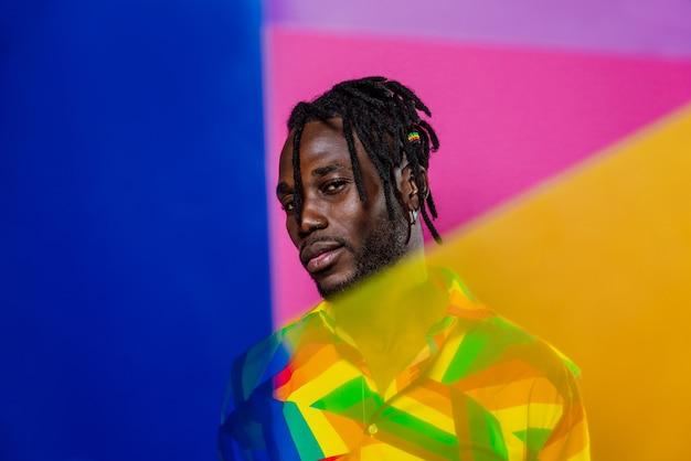 Retrato artístico com luzes de gel. homem bonito posando em fundos coloridos