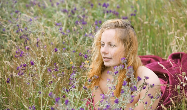 Retrato artístico de mulher sardenta em campo natural. mulher jovem, curtindo a natureza entre as flores e a grama. feche o retrato de verão