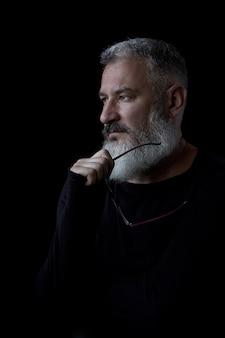 Retrato artístico de um homem de cabelos cinza brutal com barba e óculos em um fundo preto, foco seletivo