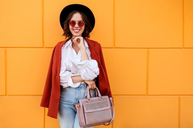 Retrato ascendente próximo ao ar livre da fêmea de cabelos curtos moreno feliz que levanta sobre a parede amarela. chapéu da moda, óculos cor de rosa, blusa branca e calça jeans.