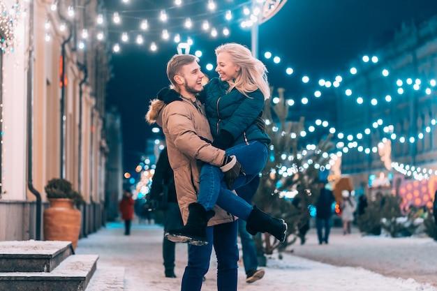 Retrato ascendente próximo ao ar livre do jovem casal lindo posando na rua.