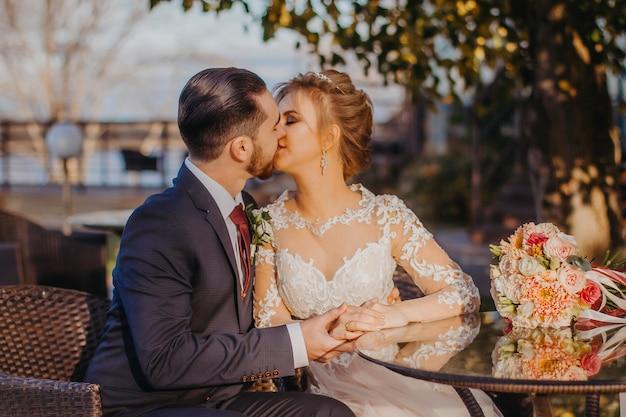 Retrato ascendente próximo dos noivos. a noiva e o noivo beijam.