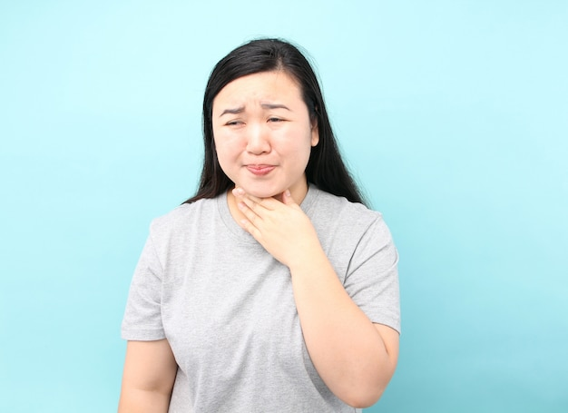 Retrato ásia mulher há uma dor de garganta, sobre fundo azul no estúdio.