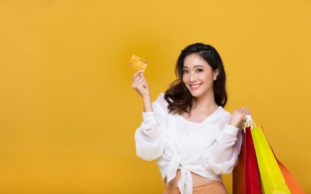 Retrato asiática feliz mulher jovem e bonita sorrindo alegre e ela está segurando o cartão de crédito e usando telefone inteligente para compras on-line com sacos de compras em fundo amarelo.