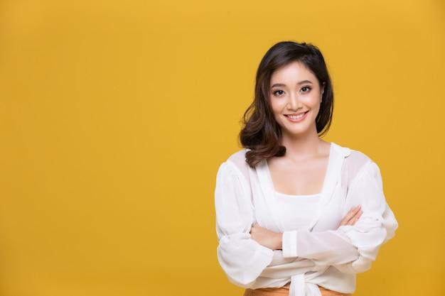 Retrato asiática feliz mulher jovem e bonita sorrindo alegre e olhando para a câmera isolada em fundo amarelo studio