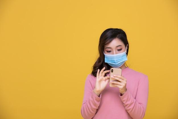 Retrato asiática feliz mulher jovem e bonita vestindo máscara facial ou máscara protetora contra crise de coronavírus ou surto de covid-19 e ela está usando telefone celular ou smartphone em fundo amarelo