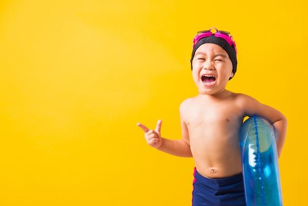 Retrato asiático criança menino usar óculos de proteção e maiô segurar anel inflável azul apontar o dedo para o outro lado