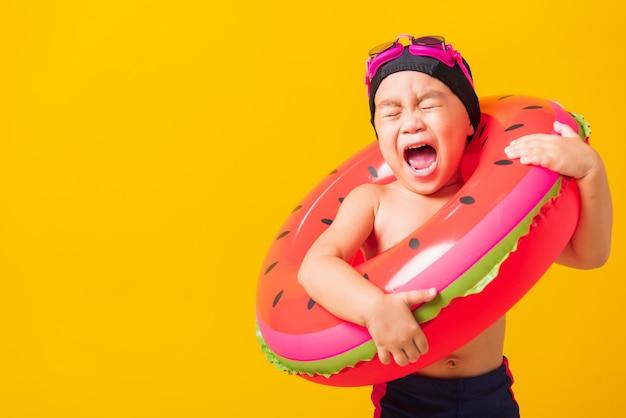 Retrato asiático criança menino usar óculos e maiô segurar anel inflável de melancia