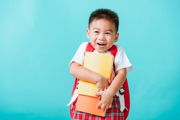 Retrato asiático feliz criança menino bonitinho da pré-escola sorrindo abraçando os livros