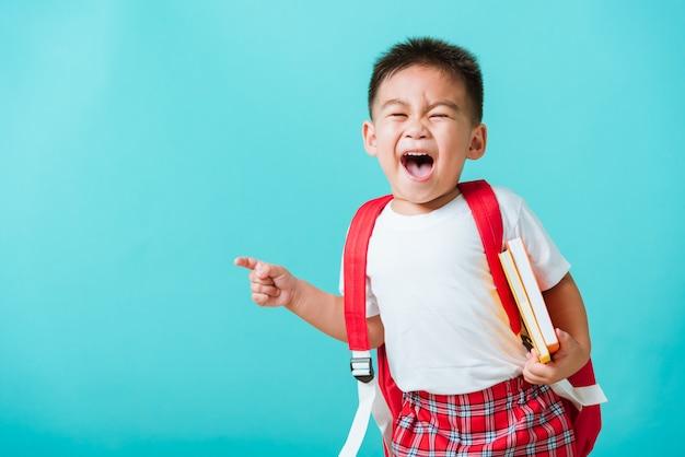 Retrato asiático feliz engraçado criança menino sorriso segurando os livros aon mão nd apontar o dedo para o espaço