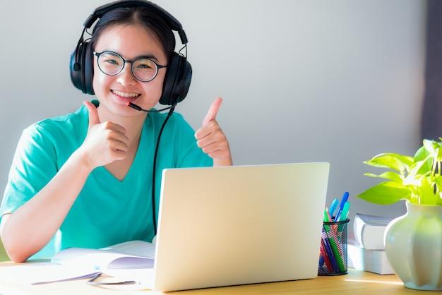 Retrato asiático jovem estudante óculos fones de ouvido estudo feliz sorriso olhando dois polegares para cima aula online faculdade aprendizagem internet educação adolescente trabalho distância em um laptop de casa