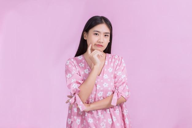Retrato asiático mulher bonita no vestido rosa e cabelo comprido preto. suas mãos tocam a bochecha, sorriem, mostram uma bela pele em fundo rosa.