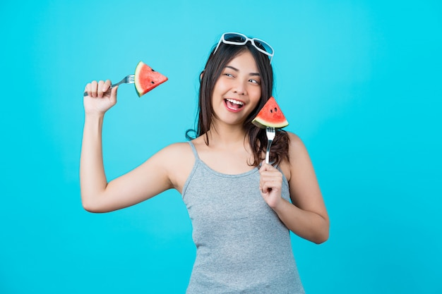 Retrato atraente jovem asiática segurando duas peças slide de melancia e usando óculos de sol da moda na parede isolada de cor azul