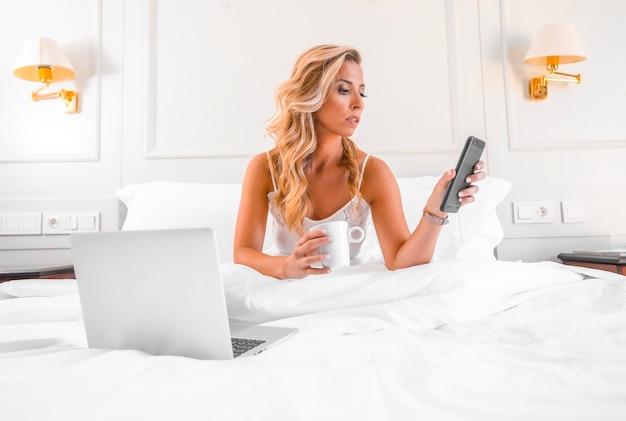 Retrato atraente jovem loira caucasiana com camisola na cama do hotel teletrabalhando com computador