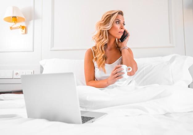 Retrato atraente jovem loira caucasiana de camisola na cama do hotel teletrabalhando com computador e telefone
