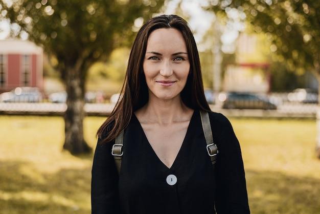 Retrato autêntico de uma mulher morena sorridente de vestido preto no parque de verão