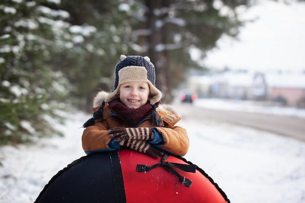 Retrato bebezinho com tubo em dia de inverno. garoto bonito brincar ao ar livre na neve.