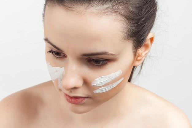 Retrato bela jovem aplicando uma máscara facial com um pincel