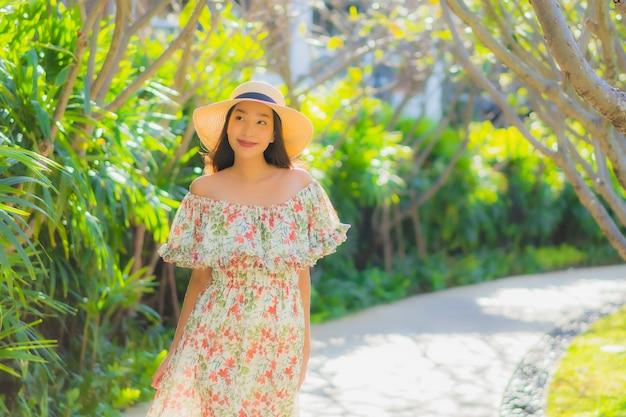 Retrato bela jovem asiática andando com feliz em torno da vista para o jardim ao ar livre