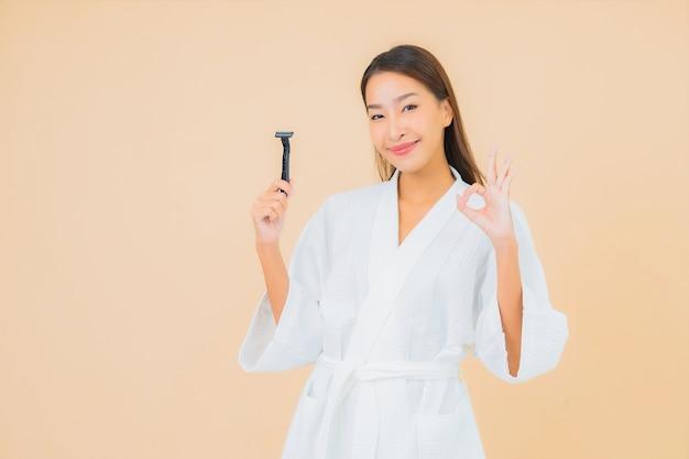 Retrato bela jovem asiática com barbear na cor bege