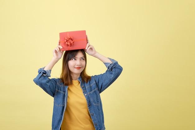 Retrato bela jovem asiática com caixa de presente vermelha em amarelo isolado