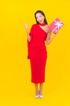 Retrato bela jovem asiática com caixa de presente vermelha