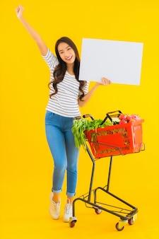 Retrato bela jovem asiática com carrinho de supermercado e mostrar tabuleiro vazio branco