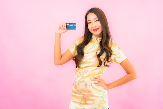 Retrato bela jovem asiática com cartão de crédito e telefone celular na parede cor de rosa