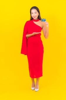 Retrato bela jovem asiática com cartão de crédito