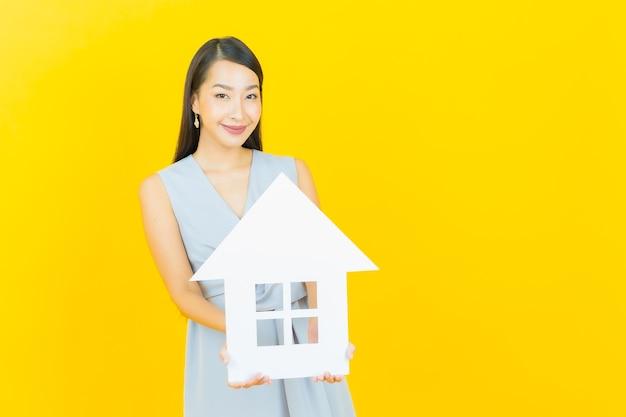 Retrato bela jovem asiática com casa ou placa de papel para casa