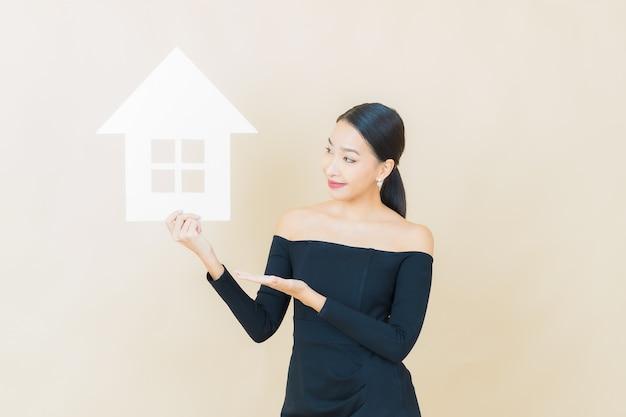 Retrato bela jovem asiática com casa ou sinal de papel em casa amarela