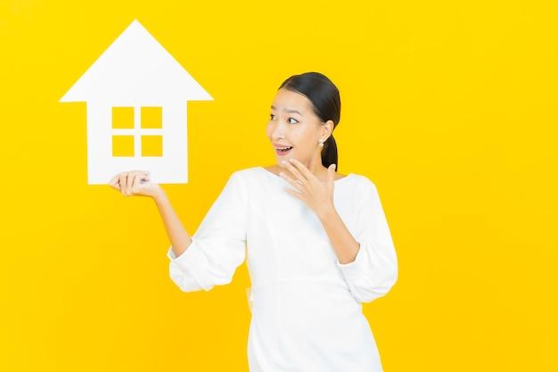 Retrato bela jovem asiática com casa ou sinal de papel em casa amarelo