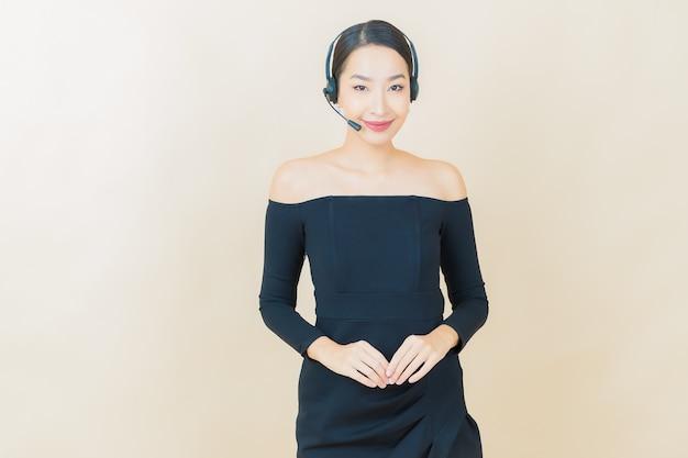 Retrato bela jovem asiática com centro de atendimento ao cliente call center em amarelo
