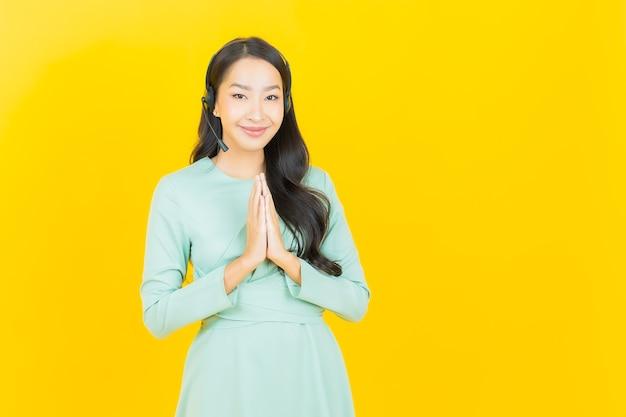 Retrato bela jovem asiática com centro de atendimento ao cliente de call center em amarelo