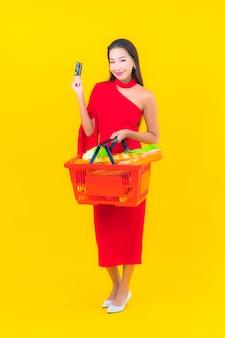 Retrato bela jovem asiática com cesta de supermercado