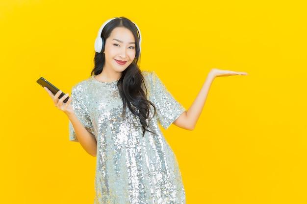 Retrato bela jovem asiática com fone de ouvido e telefone inteligente para ouvir música em amarelo