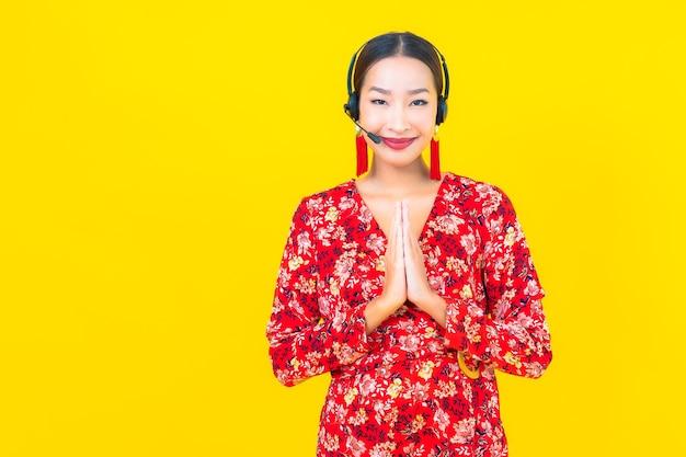 Retrato bela jovem asiática com fone de ouvido para atendimento de central de atendimento ao cliente na parede amarela