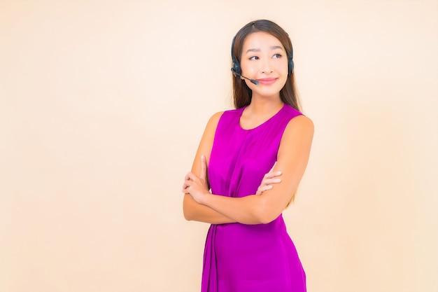 Retrato bela jovem asiática com fone de ouvido para cliente de call center na cor de fundo