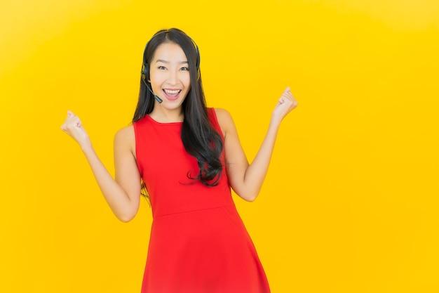 Retrato bela jovem asiática com fone de ouvido para comunicação e serviço de call center de suporte na parede amarela