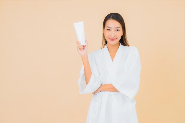 Retrato bela jovem asiática com frasco de loção e creme facial em bege