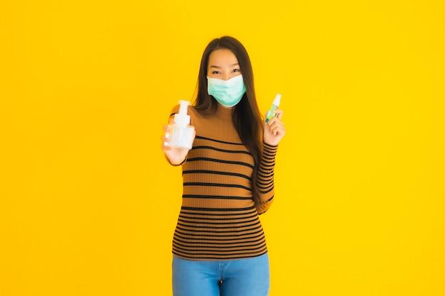 Retrato bela jovem asiática com máscara álcool spray e frasco de gel na mão para proteger de coronavírus ou covid19