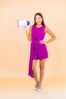 Retrato bela jovem asiática com megafone na cor de fundo isolado