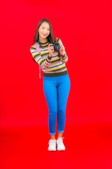 Retrato bela jovem asiática com mochila para câmera e mapa na parede vermelha isolada